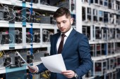 Photo handsome young businessman reading business documents at cryptocurrency mining farm