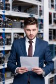 Photo serious young businessman reading business document at cryptocurrency mining farm