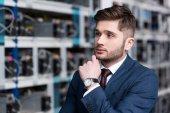Nachdenklicher junger Geschäftsmann mit der Hand am Kinn auf Kryptowährungsfarm