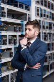 Photo thoughtful young businessman with hand on chin at ethereum mining farm