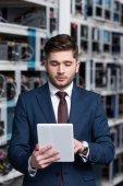 schöner junger Geschäftsmann mit Tablet auf dem Bergbaubetrieb von Ethereum