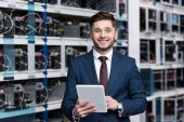 Lächelnder junger Geschäftsmann mit Tablet auf Bergbaufarm von Ethereum