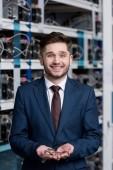 Glücklicher junger Geschäftsmann mit einem Haufen Bitcoins in der Hand auf Kryptowährungs-Mining-Farm
