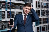 Photo failed young businessman showing smartphone at cryptocurrency mining farm
