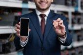 Schnappschuss von Geschäftsmann zeigt Smartphone und Bitcoin auf Kryptowährungsfarm