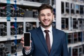 Photo happy young businessman showing smartphone at cryptocurrency mining farm