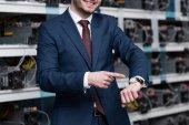 Schnappschuss eines lächelnden Geschäftsmannes, der auf die Armbanduhr der Minenfarm von Ethereum zeigt
