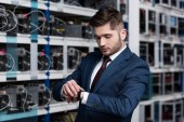 Photo handsome young businessman looking at wristwatch at ethereum mining farm