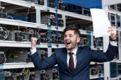 Photo happy young businessman with papers celebrating victory at cryptocurrency mining farm