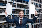 Photo successful young businessman with papers celebrating victory at cryptocurrency mining farm