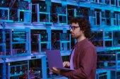 Junge Computeringenieurin arbeitet mit Laptop auf Bergbaufarm von Ethereum