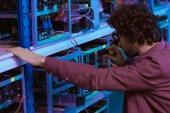 Fotografie Nahaufnahme eines jungen Computeringenieurs, der mit einem Schraubenzieher auf einem Bergbaubetrieb von Ethereum repariert