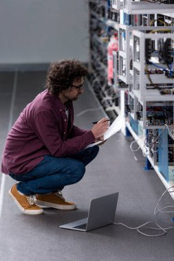 serious computer engineer working while sitting on floor at cryptocurrency mining farm