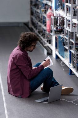 computer engineer working while sitting on floor at cryptocurrency mining farm
