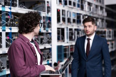 businessman and computer engineer working together at ethereum mining farm