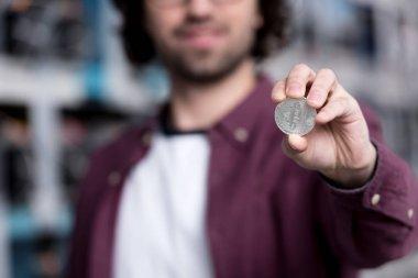 close-up shot of computer engineer holding bitcoin