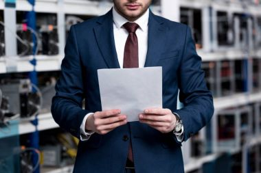 cropped shot of young businessman with paperwork at cryptocurrency mining farm