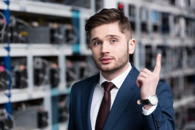 handsome young businessman with creative idea pointing up at cryptocurrency mining farm