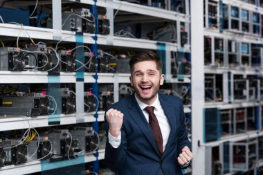 happy young businessman celebrating victory and raising fist at cryptocurrency mining farm