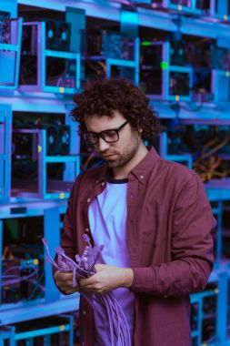 handsome computer engineer with ethernet wires at ethereum mining farm