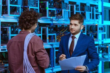 handsome businessman and computer engineer working together at cryptocurrency mining farm