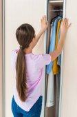 Fotografie zadní pohled na mladou ženu otevírání skříně s oblečením doma