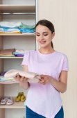 Fotografie attractive young woman holding folded shirt in front of cabinet