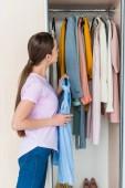 Fotografie atraktivní mladá žena, výběrem oblečení z kabinetu doma