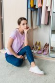 Photo thoughtful young woman sitting near cabinet with clothes and shoes at home