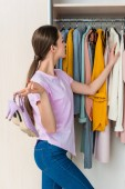 Fotografie attractive young woman holding shoes and choosing clothes from cabinet at home