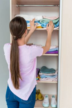 attractive young woman choosing clothes from stack