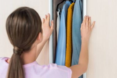 close-up shot of young woman opening cabinet with clothes at home