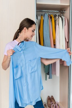 smiling young woman looking at shirt on hanger