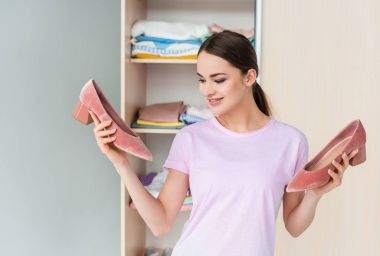 happy young woman holding heels in front of cabinet at home
