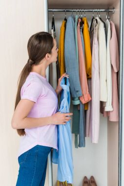 attractive young woman choosing clothes from cabinet at home
