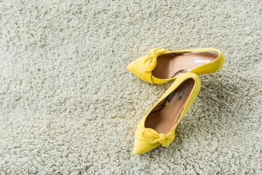 top view of stylish yellow high heels on carpet
