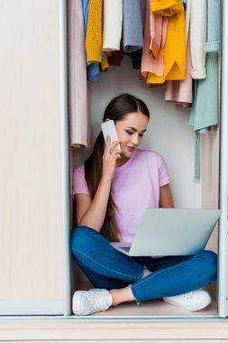 attractive young woman sitting inside of cabinet and working with laptop at home