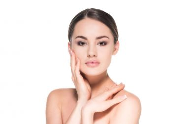 beautiful young woman with clear skin touching her face isolated on white