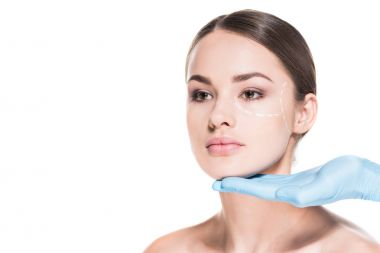 doctor touching face of beautiful woman with dotted line for plastic surgery isolated on white