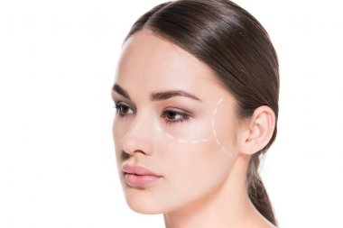 attractive young woman with dotted line drawn on face for plastic surgery isolated on white