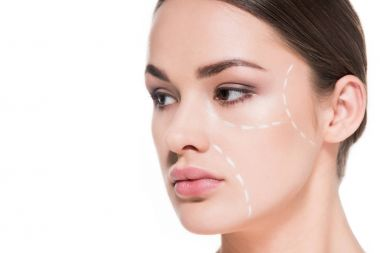 beautiful young woman with dotted line drawn on face for plastic surgery isolated on white
