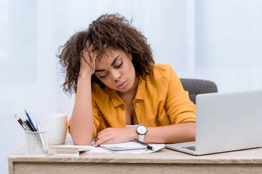 overworked young woman sitting at workplace in office