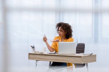 angry young woman looking at smartphone at workplace