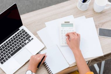 cropped shot of woman working with calculator at workplace