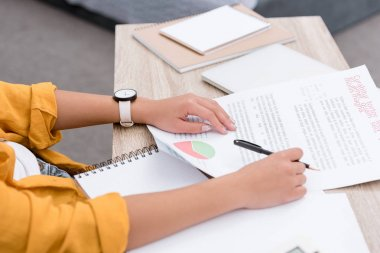 cropped shot of woman doing paperwork at workplace