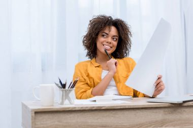 happy thoughtful young woman doing paperwork
