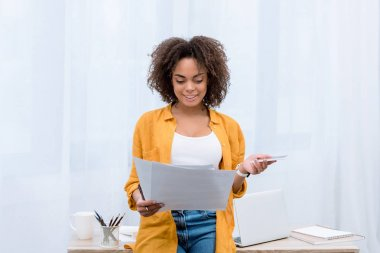 happy young woman reading documents at office