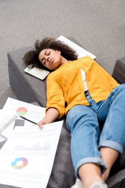 overworked young woman sleeping on couch after work at home