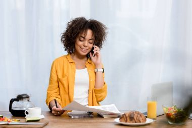 young african american woman working at home with various food on table