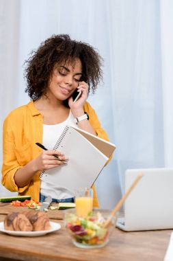 happy young woman with notebook talking by phone at home